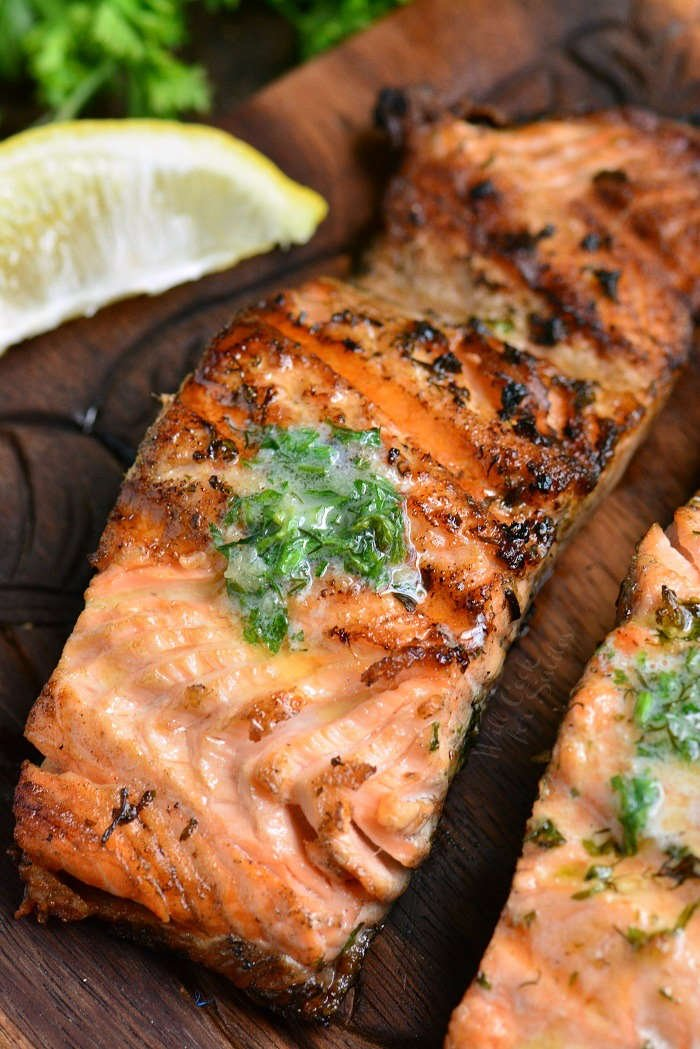 easy grilled salmon with herb butter on a wooden board with a lemon