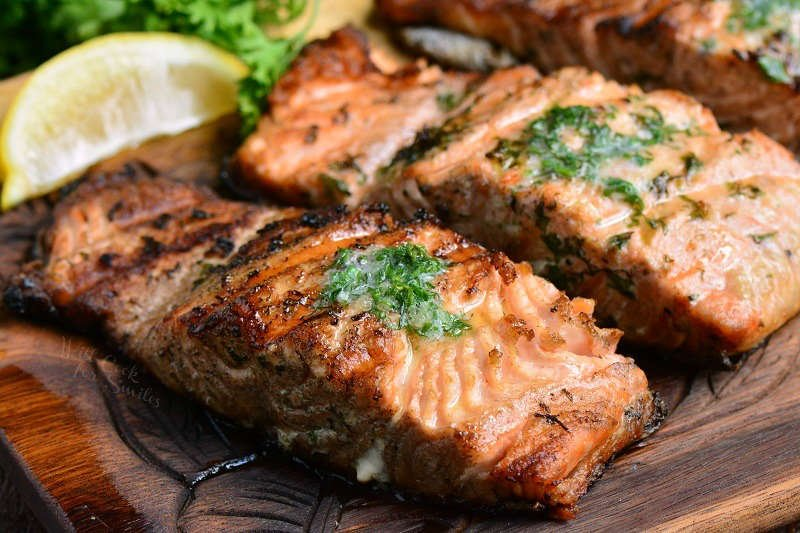grilled salmon with butter on a wooden cutting board
