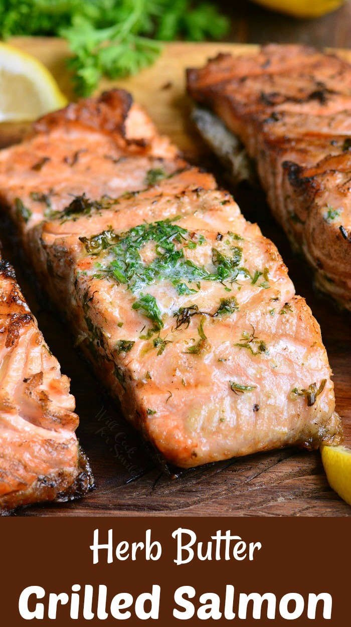 grilled salmon with herb butter on a wood cutting board