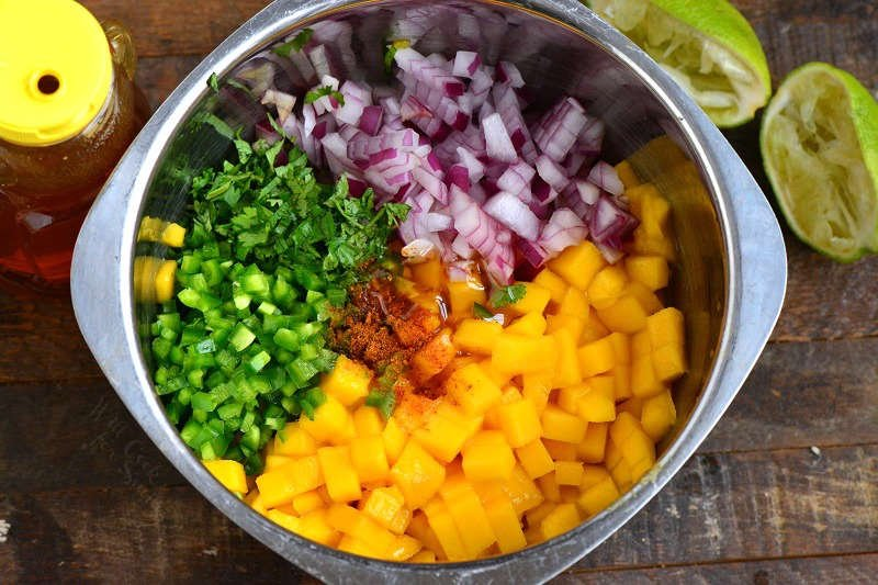 ingredients in mango salsa in a metal bowl on a wood cutting board