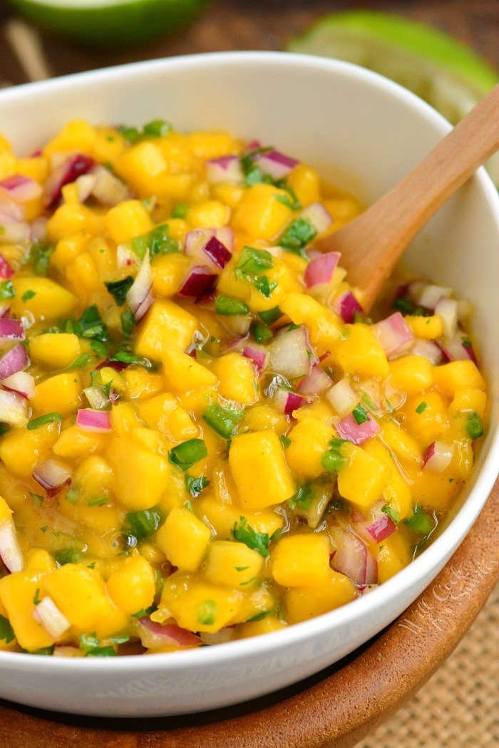Mango salsa in a bowl with a wood bowl