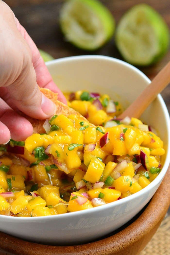 mango salsa in a bowl and scooping with a chip