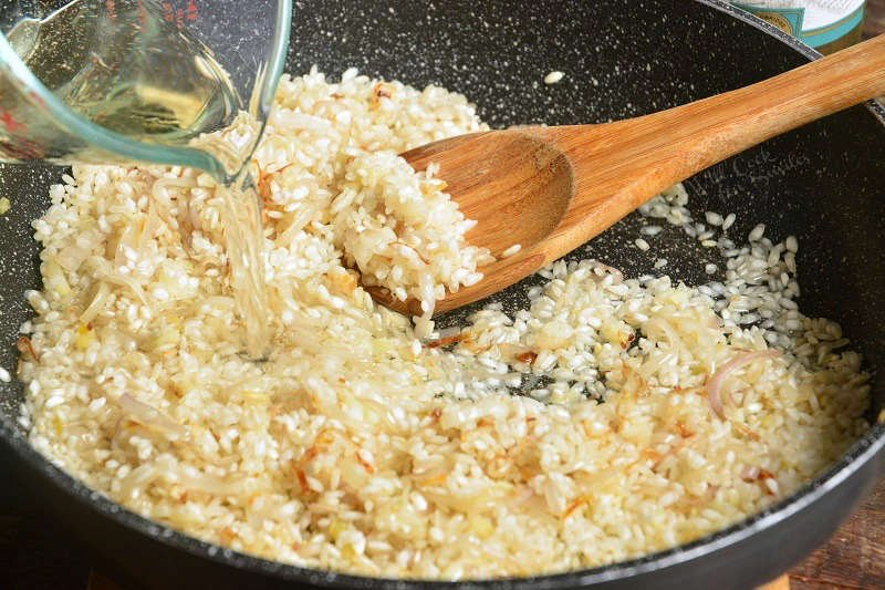 adding liquid to the risotto that is in a pan with a wooden spoon