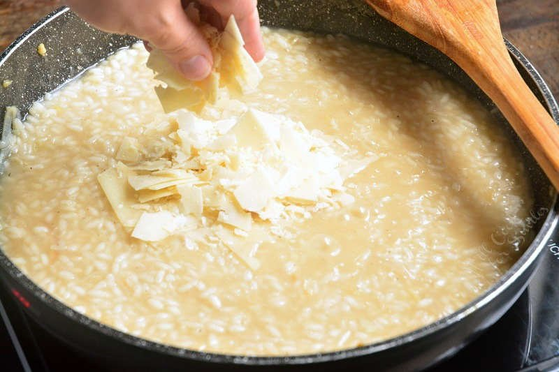 adding Parmesan cheese a couple of minutes before risotto is ready into a pan with a wooden spoon