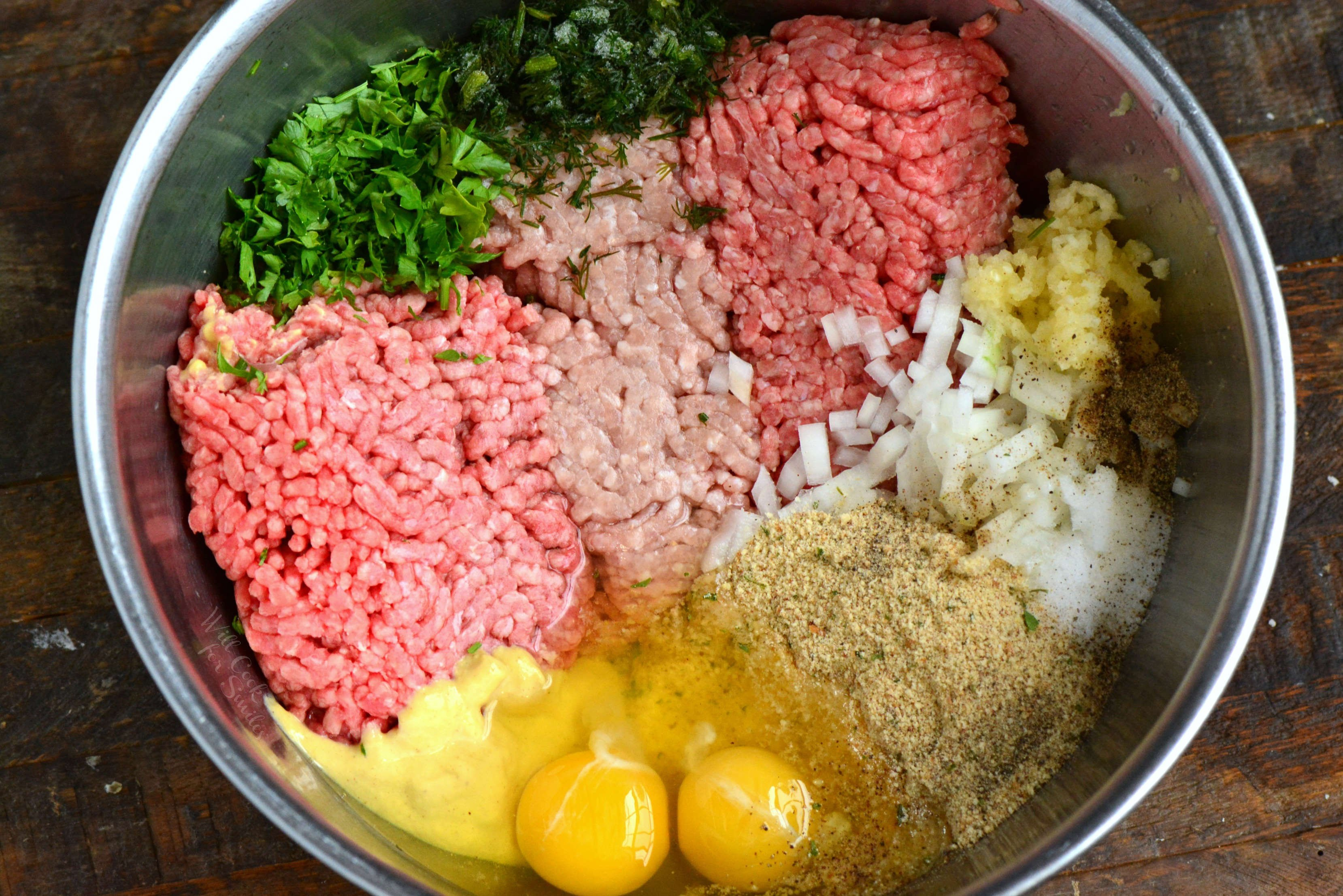 ingredients for the meatloaf in a metal bowl