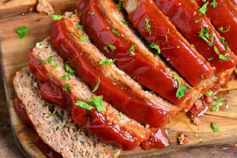 horizontal image of sliced meatloaf topped with ketchup glaze