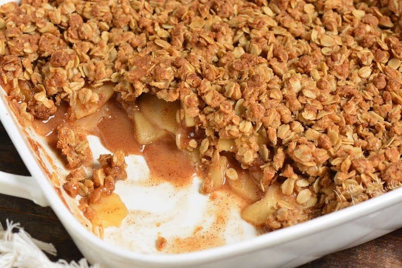 baked apple crisp with a piece taken out in a baking dish