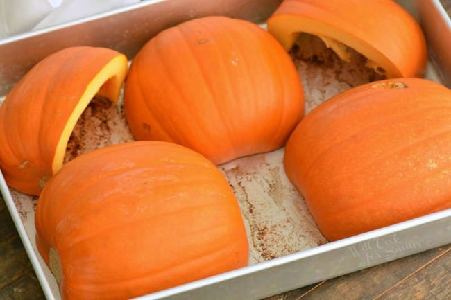 pumpkin halves in a roasting pan cut side down with some cinnamon on the bottom