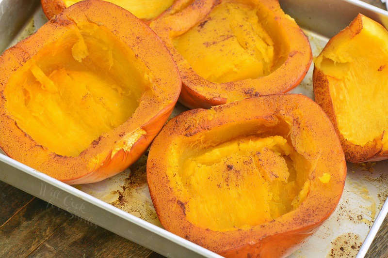 cooked pumpkin halves in a baking pan turned cut side up