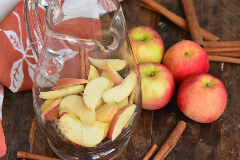 apple in a pitcher sitting on a wood table with apples and cinnamon sticks