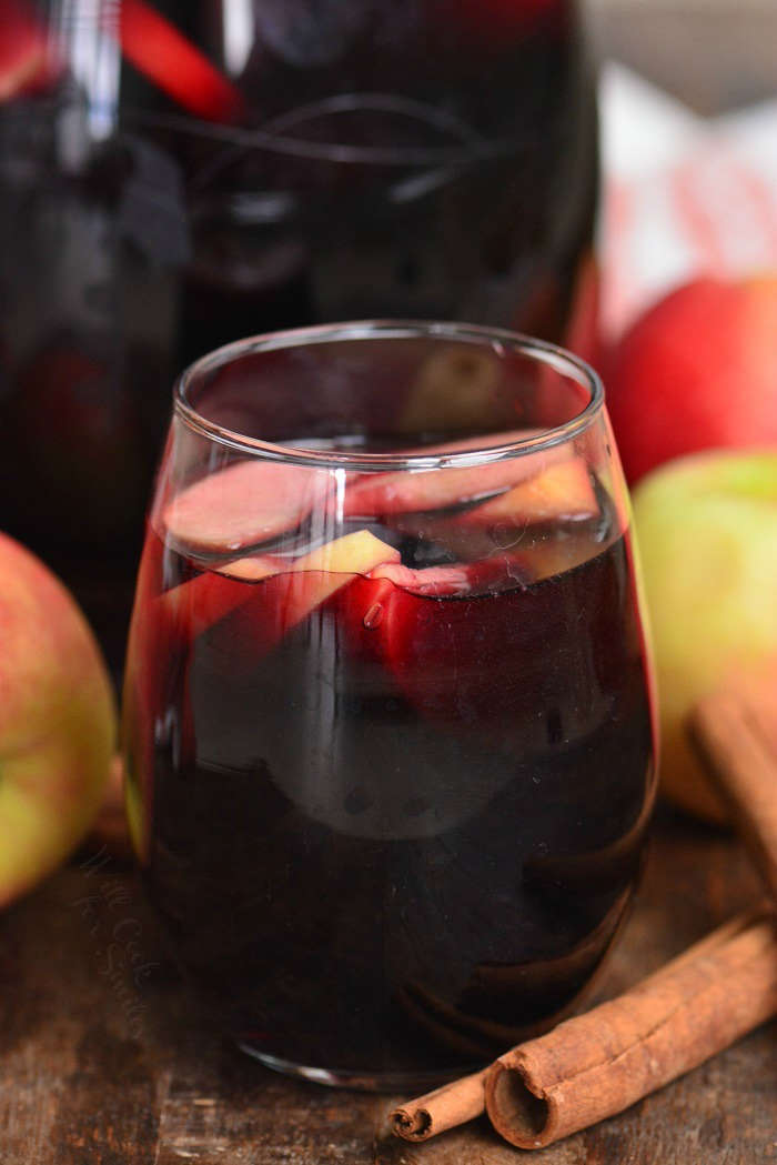 apple sangria in a wine glass on a wood table with apples and cinnamon sticks