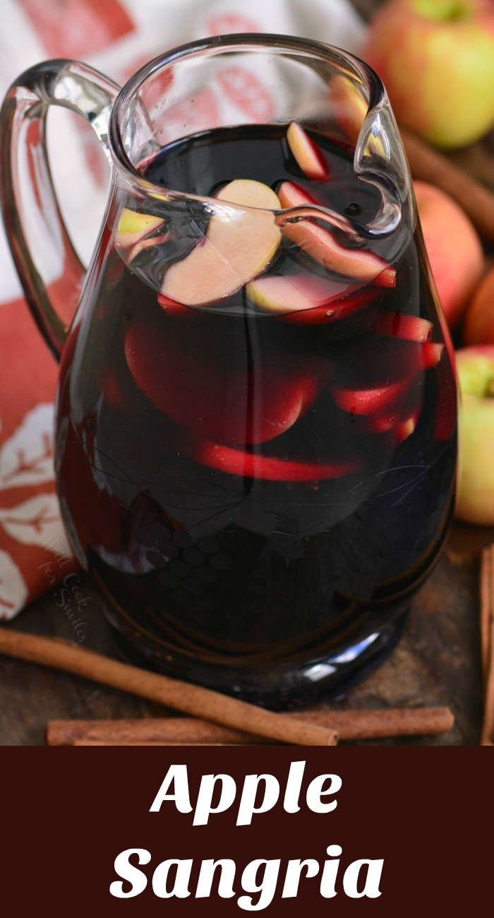apple sangria in a pitcher on a wood cutting board with cinnamon sticks and apples