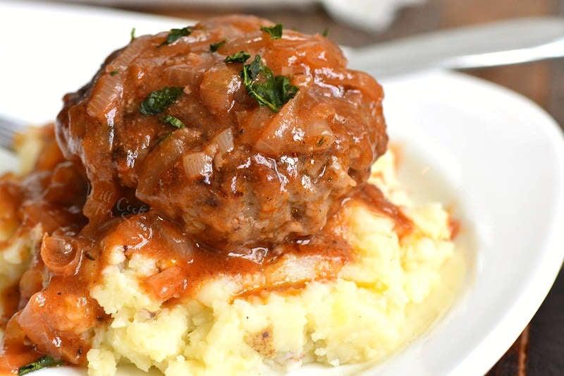 saliabury steak over mashed potatoes on a plate