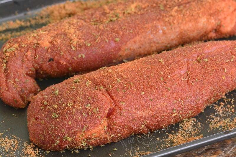 pork tenderloin coated in pork dry rub on a baking sheet
