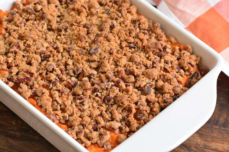sweet potato casserole with pecan topping on a wood cutting board