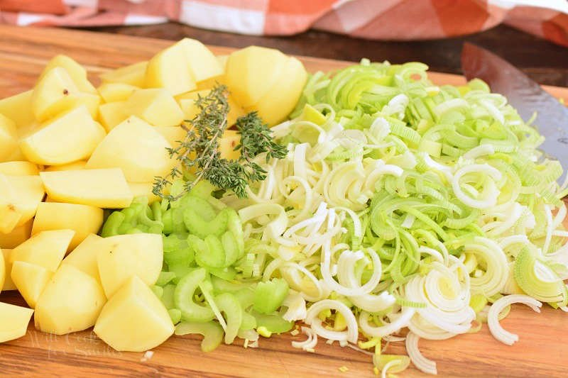 ingredients for potato leek soup on a wood cutting board