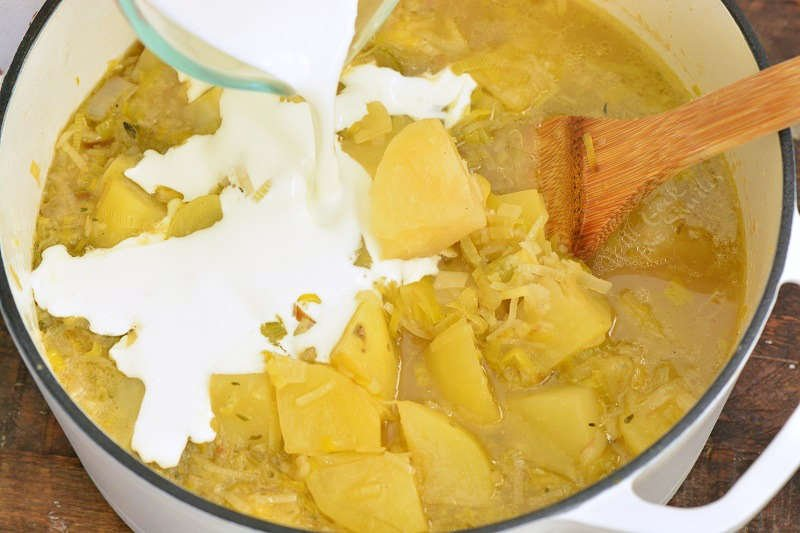 adding cream to cooked soup that is in a pot with a wooden spoon