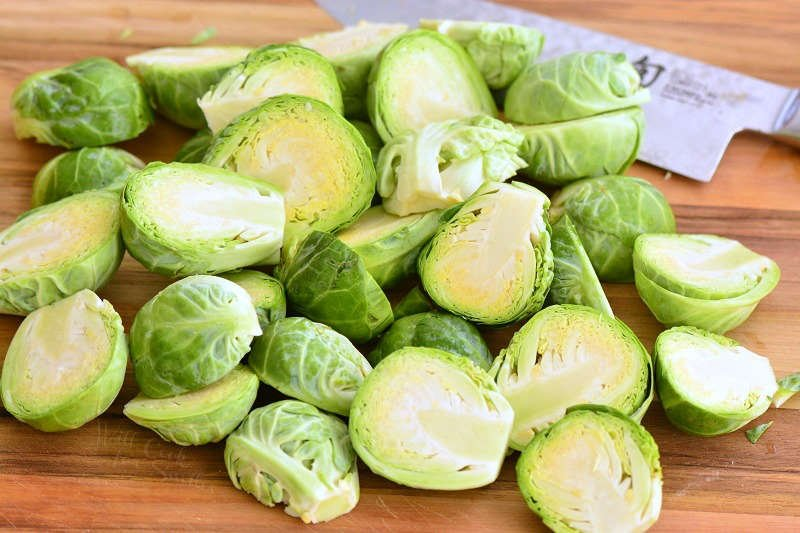 sliced brussels sprouts on a wood cutting board with a knife