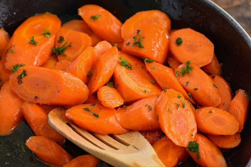 honey glazed carrots in a pan with a wooden spoon
