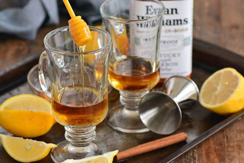 adding honey to the whiskey in a glass with lemons and whiskey on a baking sheet