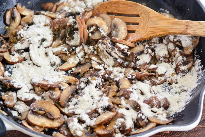 adding flour to pan of mushrooms, and stirring with a wooden spoon