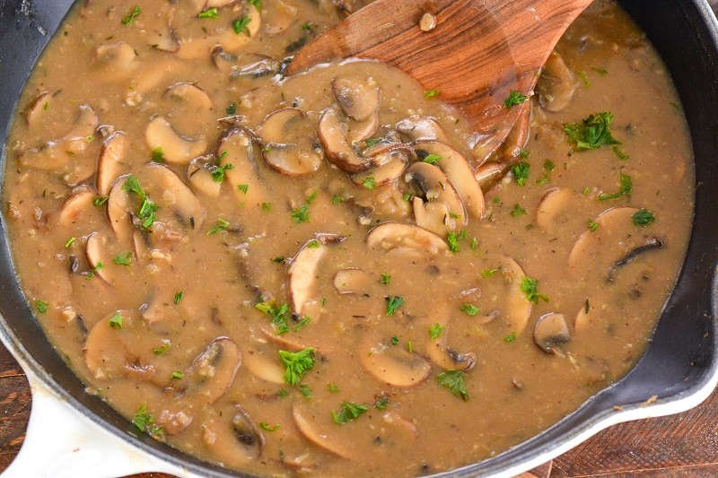 mushroom gravy in a cast iron skillet with a wooden spoon