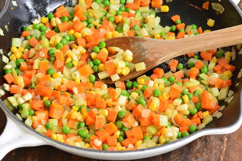 vegetables for turkey pot pie in a cast iron skillet with a wood spatula