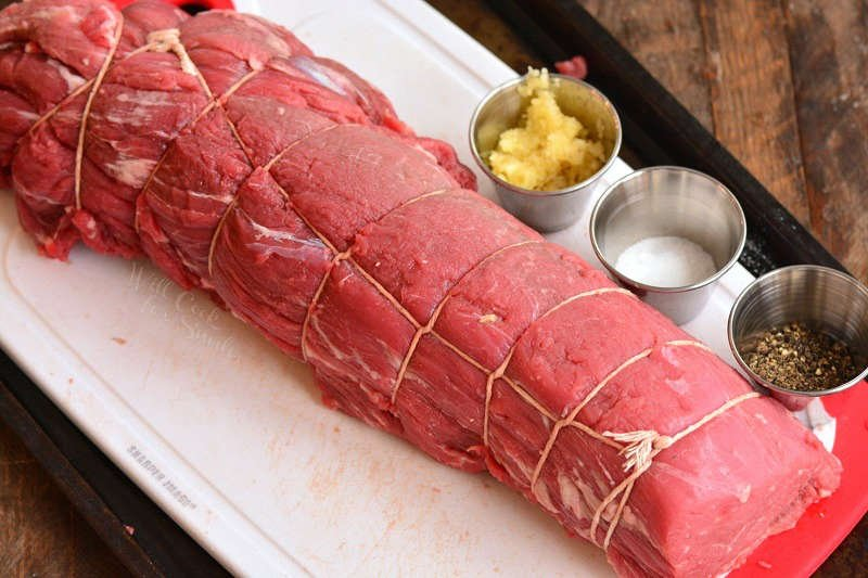 cleaned and tied beef tenderloin on a plastic cutting board with seasoning