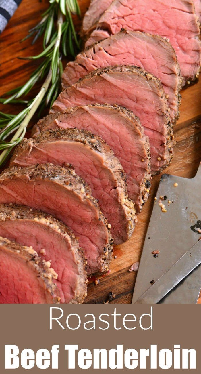 beef tenderloin sliced on a wood cutting board with a sprig of rosemary