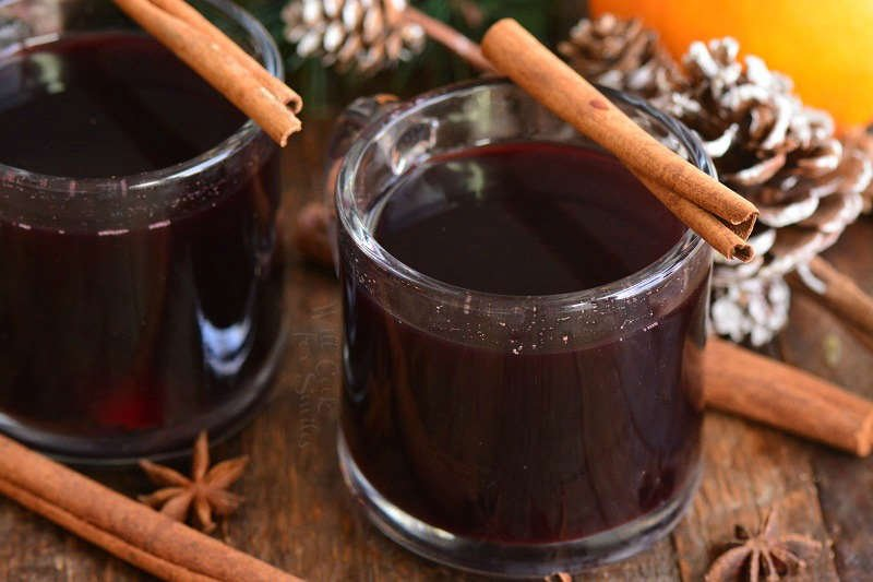 mulled wine in mugs, horizontal with cinnamon sticks over cups