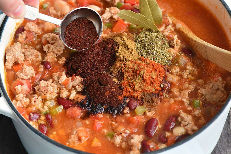 adding spices to chili in a pot