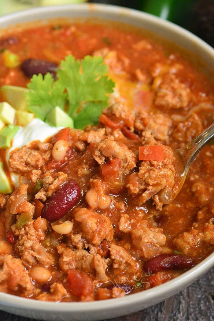close up of spooning out turkey chili out of the bowl