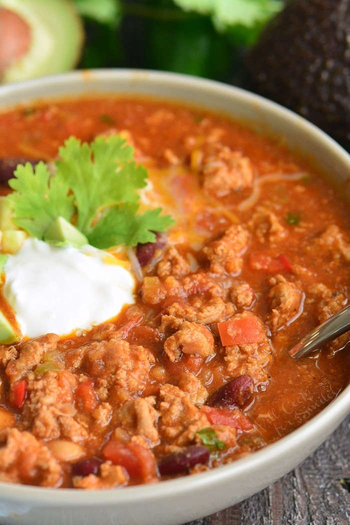 spooning turkey chili in a bowl