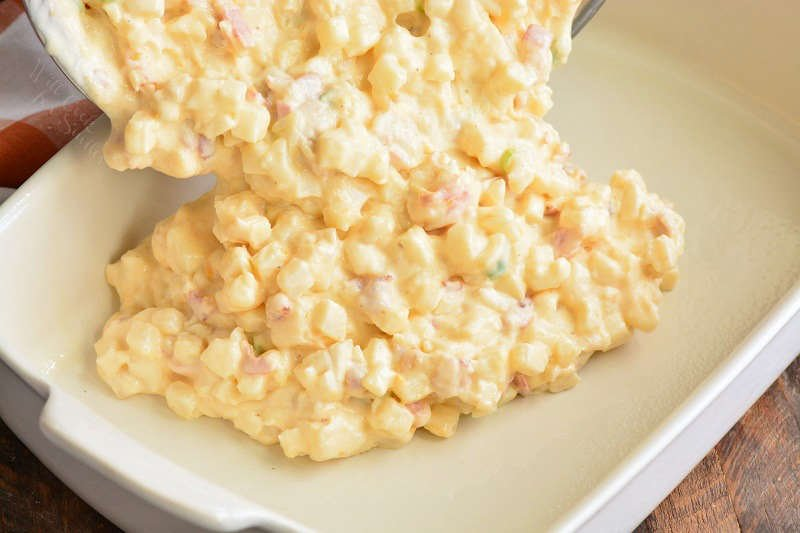 spreading potatoes and cheesy sauce in the baking pan