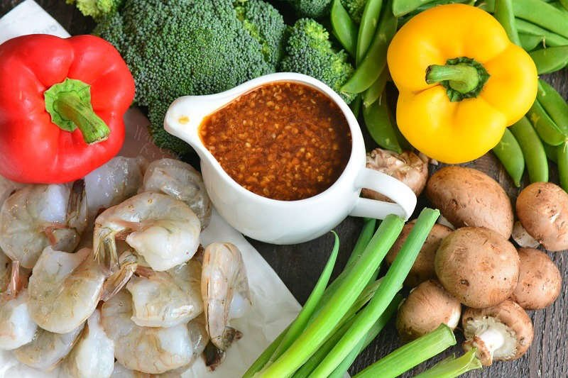 ingredients for shrimp stir fry on a wood table