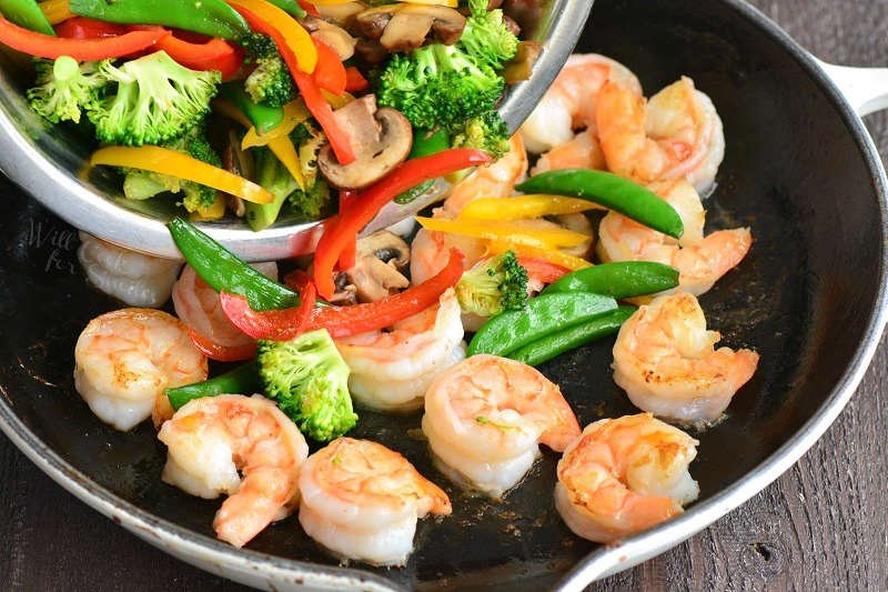 adding vegetables to shrimp in a pan