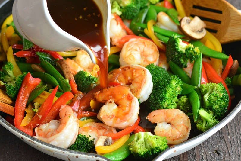 pouring stir fry sauce into the pan
