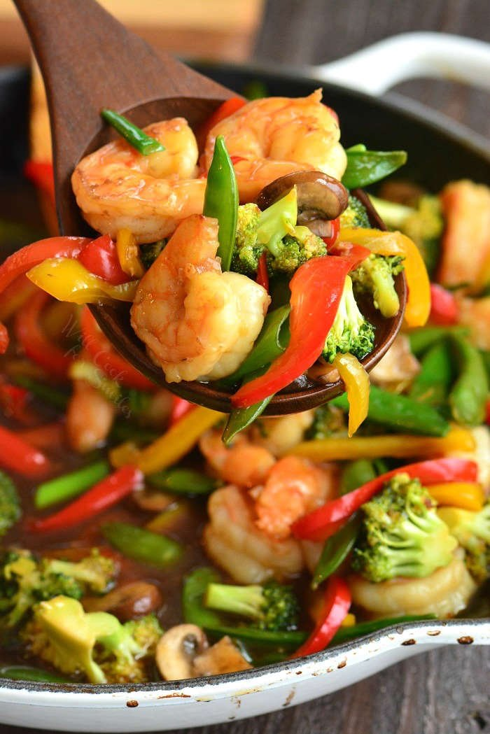 spoonful of shrimp stir fry in a pan