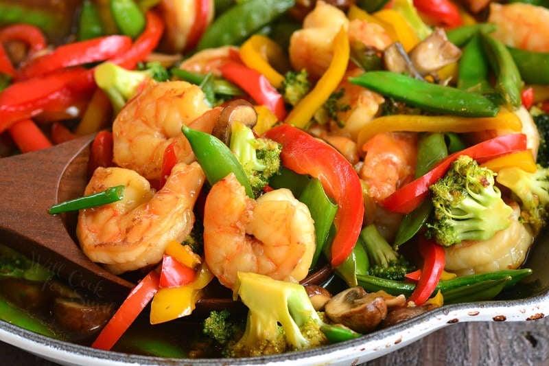 shrimp stir fry horizontal with a wooden spoon