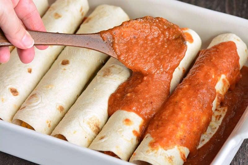 spreading sauce over rolled enchiladas