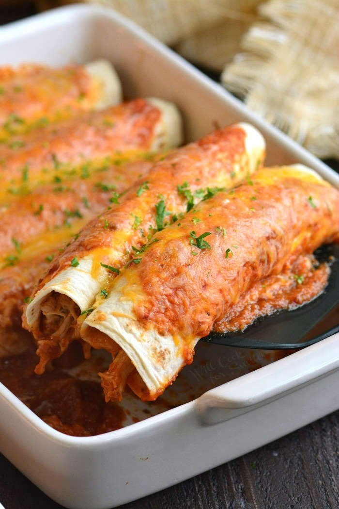 pulling enchiladas out of the pan