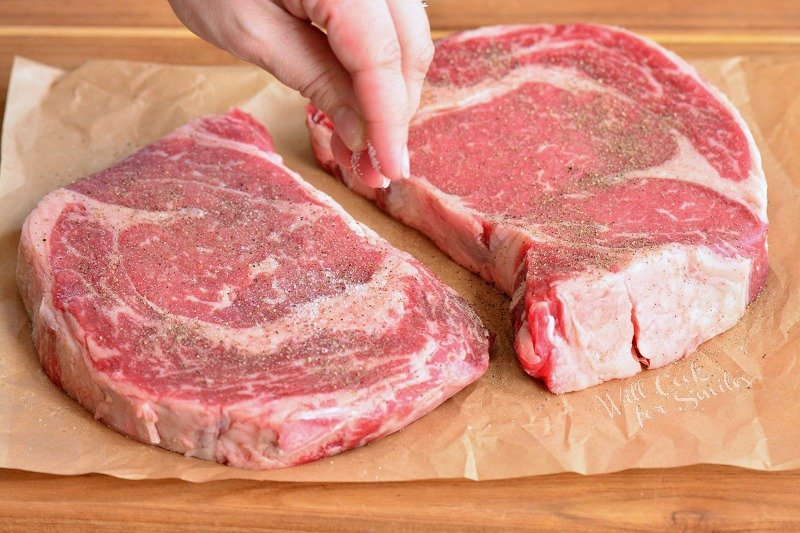seasoning ribeye steaks with salt and pepper