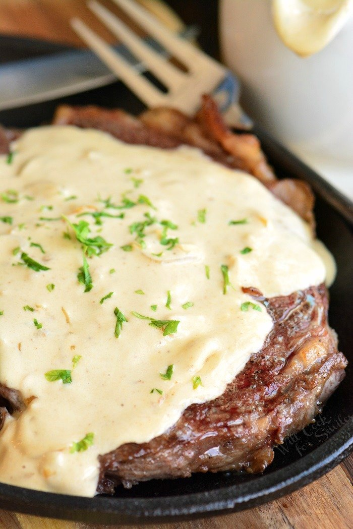 vertical photo of steak topped with cream sauce