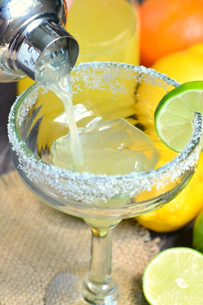 pouring margarita into a glass