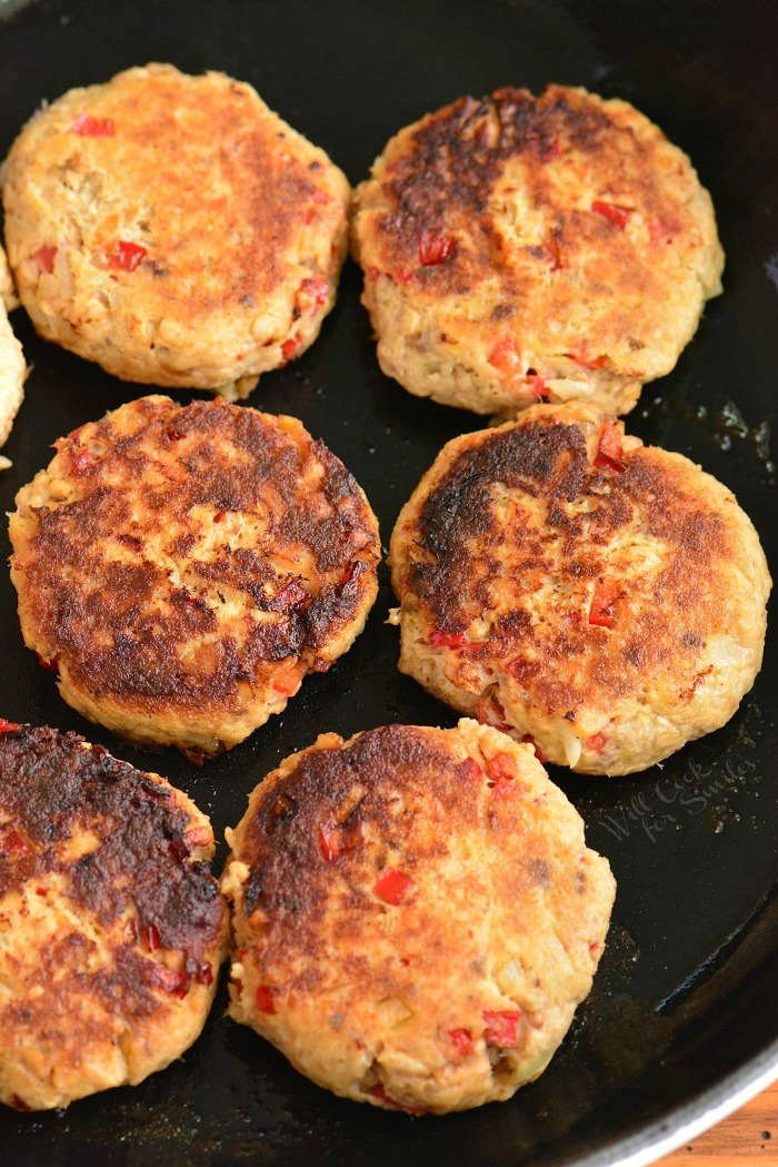 cooked salmon patties in the pan vertical view