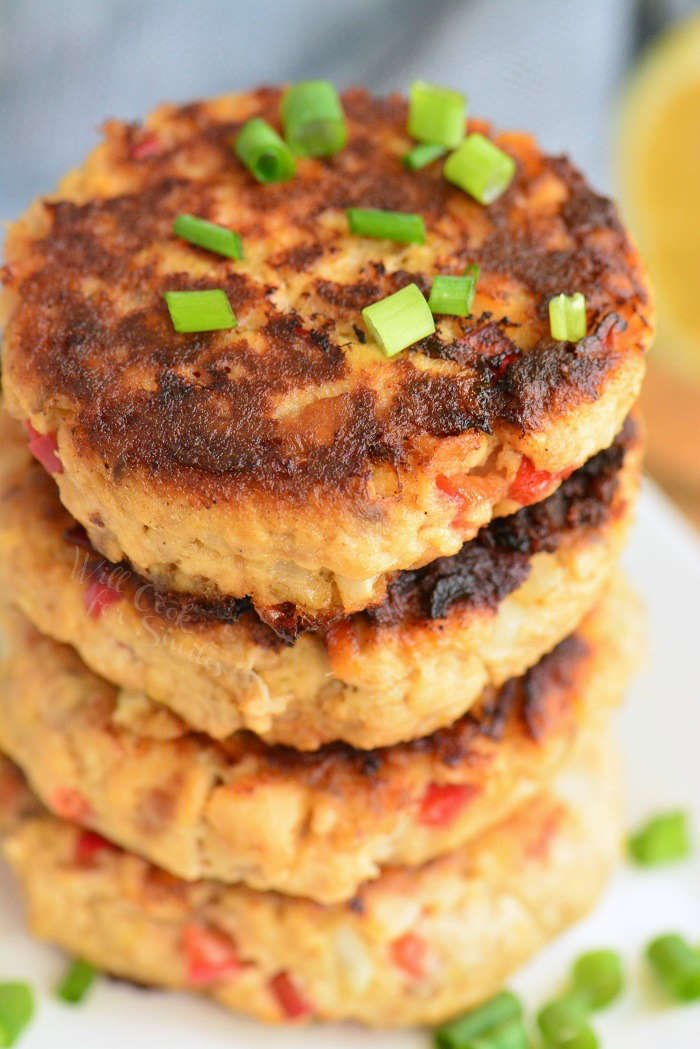 stacked cooked salmon patties with green onion sprinkled on top