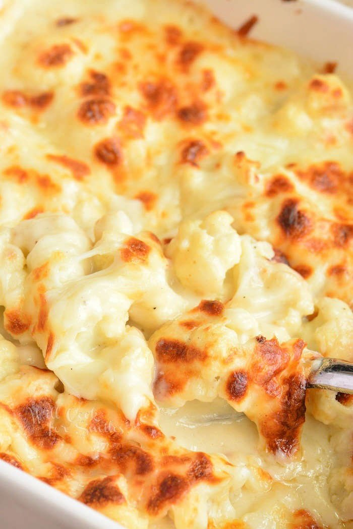 scooping out cheesy baked cauliflower