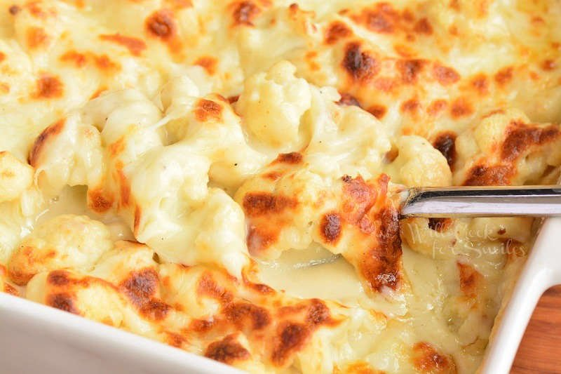 scooping cooked baked cheesy cauliflower