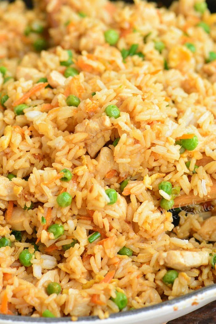 starting to scoop cooked chicken fried rice from the pan with a wooden spoon