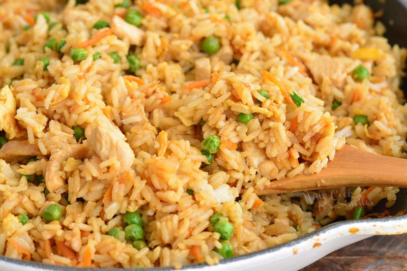 cooked chicken fried rice in the pan with wooden spoon scooping the rice